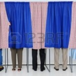 15608536-a-row-of-five-voting-booths-with-men-and-women-casting-their-ballots-at-a-polling-place-horizontal-f